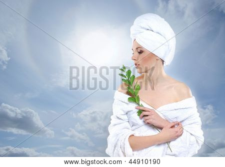 Young beautiful woman in towel getting spa treatment over the heaven background