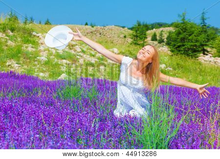Pretty girl sitting down on purple lavender field, enjoying warm sun light, holding in hand white summer hat, summertime nature, holiday and vacation concept