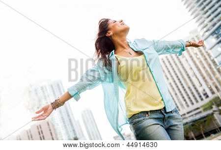Beautiful urban woman enjoying her freedom with arms open