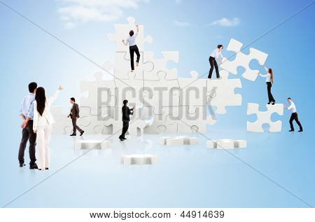 Business teamwork in action creating a puzzle on the cloud