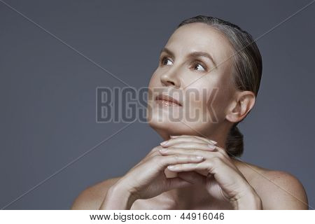Portrait of 40 year old woman with beautiful skin and natural makeup on studio background with copy space over gray