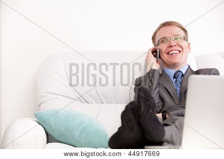 Young handsome man in suit sitting on sofa and talking on phone smiling in living room