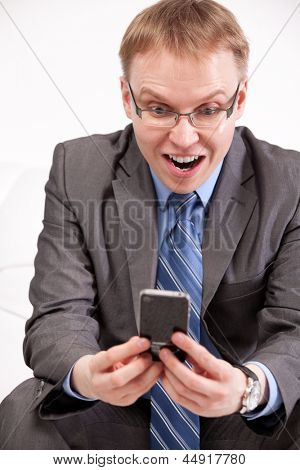 Closeup portrait of amazed man using cell phone on white background
