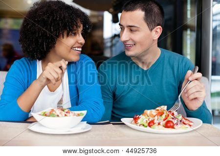 Happy young couple having lunch in restaurant