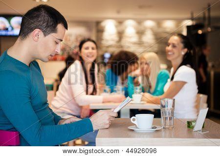Group of girl watching handsome man in cafe, man ignoring girls