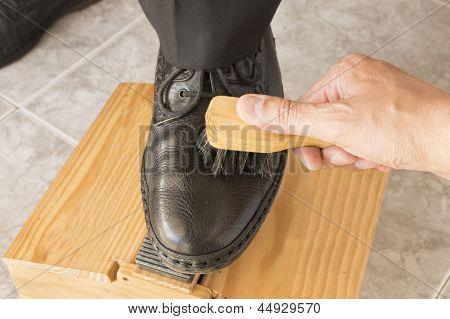 shoe shiner brushing a businessman shoe