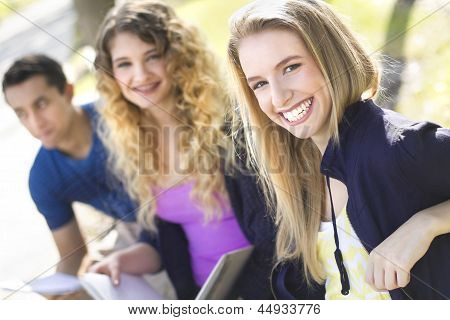 Group Of Students Sitting On A Bench