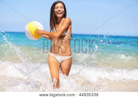 Beach woman having fun laughing enjoying sun in bikini running at with water spray splashing and a beach ball in her hands laughing happy. Beautiful joyful cheerful multiracial asian caucasian girl.