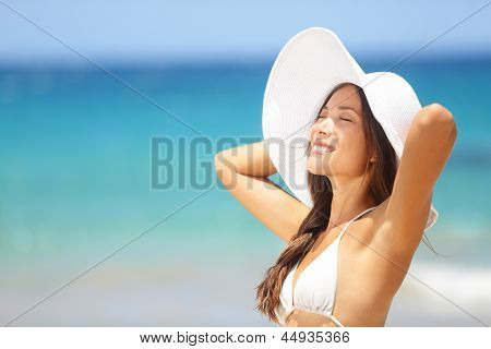 Relaxing beach woman enjoying the summer sun happy standing in a wide sun hat at the beach with face raised to the sunlight. Head and shoulder portrait. Multicultural Asian Caucasian in enjoyment.