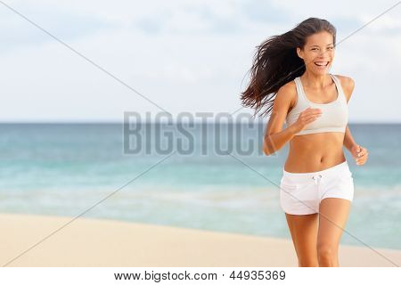 Woman runner running happy on beach laughing having fun while jogging and training for marathon run. Beautiful young mixed race Chinese Asian Caucasian female fitness model working out outside.
