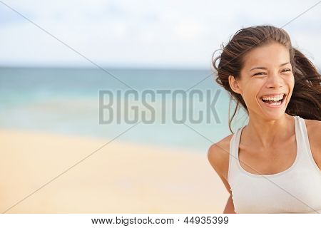 Beach fun - happy running woman closeup with copy space. Smiling joyful elated girl jogging and laughing while training outdoors on beautiful beach. Mixed race Asian Chinese / Caucasian female model.