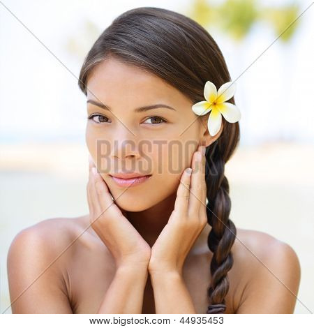 Spa resort beauty portrait of woman looking at camera serene outside. Beautiful skin care concept with multiethnic model girl with perfect skin.
