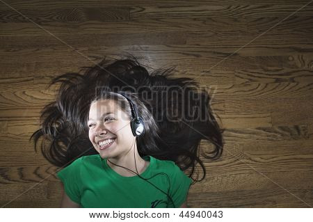 Teenage girl lying on the floor wearing headphone and smiling