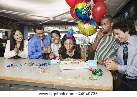 Woman blowing out birthday candles at office party