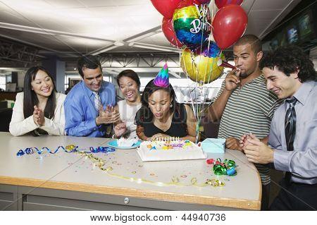 Mulher, soprando velas de aniversário em festa de escritório