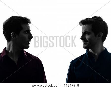 two caucasian young men looking at each others in shadow  white background