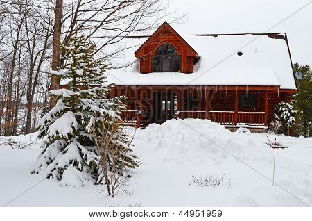 Log cabin on a heavy snow laden day