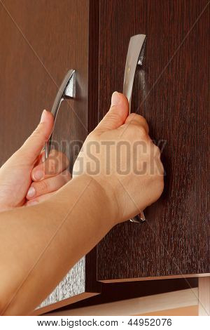 Women's hands are open cabinet doors