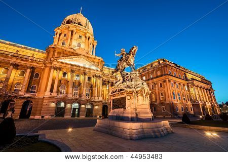 The Illuminated Main Facade Of The Buda Castle In Budapest At Night
