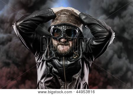 pilot with glasses and vintage hat over background explosion