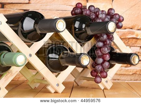 Bottles of wine placed on wooden stand on stone wall background