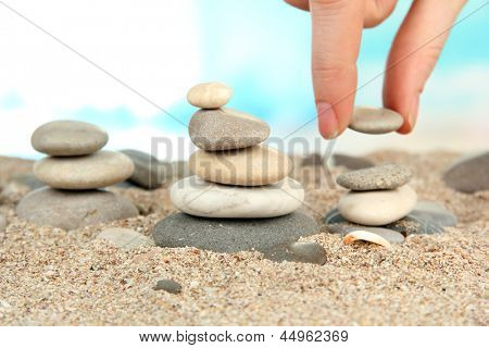 Hand baut Turm des Meeres Steine auf Sand auf hellem Hintergrund