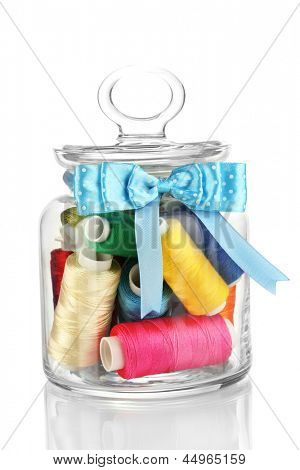 Glass jar containing various colored thread isolated on white