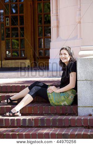 Young Teen Girl Enjoying Sunshine, Sitting On Brick Steps Outdoors