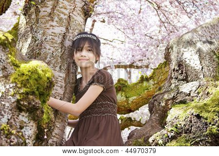 Girl sitting on moss covered branches of  flowering cherry tree