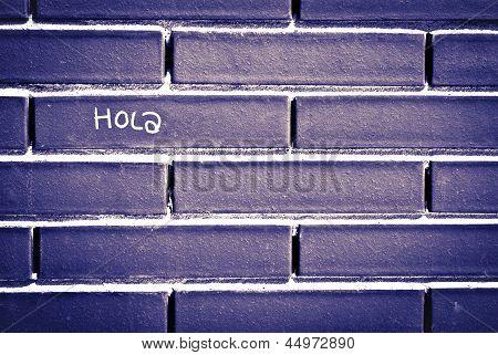 Espanhol Olá 'hola' escrito sobre tijolo para parede