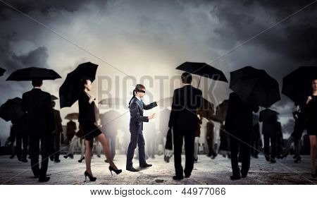 Image of businessman in blindfold walking among group of people