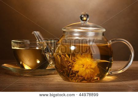 glass teapot and cup with exotic green tea on wooden table on brown background