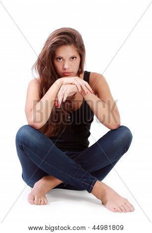 Young Brunette Woman Sits On Floor With Bended Knees Isolated On White Background.