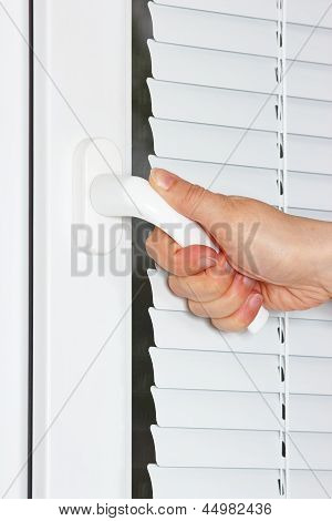 Hand opens the white plastic window with shutters