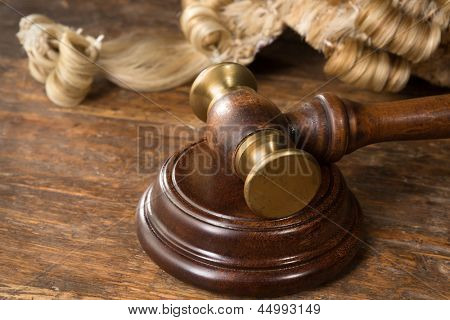 Wooden block, judge's wig and gavel on a wooden desk