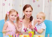 Happy young family playing with colorful paint at home, mother with two adorable children decorate E