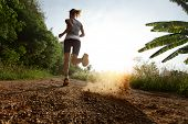 foto of off_road  - Young lady running on a rural road during sunset - JPG
