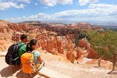 image of hoodoo  - Hikers in Bryce Canyon resting enjoying view Hiking couple in beautiful nature landscape with hoodoos - JPG