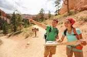 People hiking looking at hike map in Bryce Canyon. Young multiracial couple of hikers navigating and