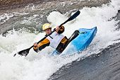 stock photo of rough-water  - an active male kayaker rolling and surfing in rough water - JPG