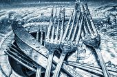 Blue toned forks and knives washed on a kitchen sink