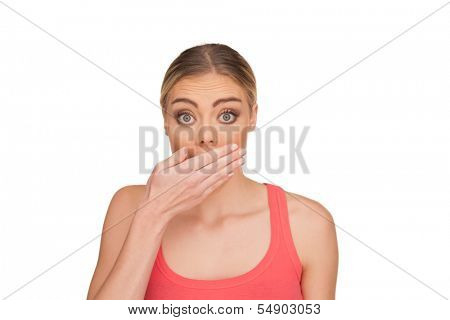 Portrait of a surprised blond woman covering the mouth with the hand in disbelief and eyes wide open wearing a red tank top on a white background