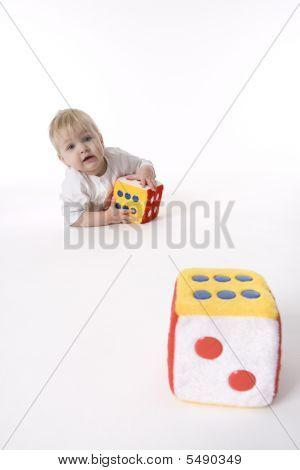 Baby Girl Is Playing With Two Soft Toy Dices On White Background