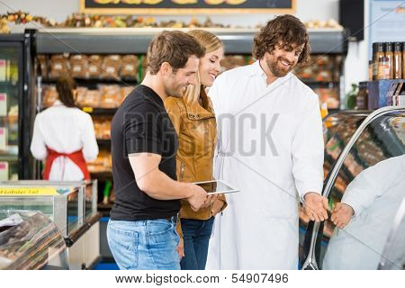 Happy salesman assisting couple in buying meat at butcher's shop