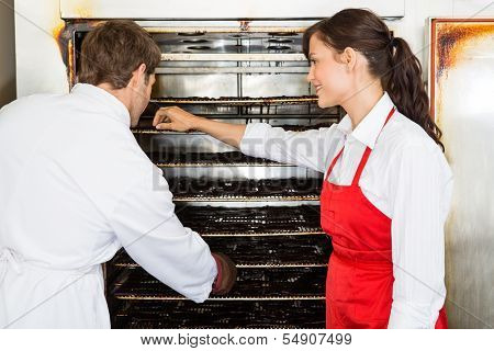 Male and female workers drying meat slices in oven at butcher's shop