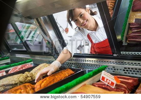 Portrait of smiling saleswoman picking meat displayed in cabinet at butcher's shop
