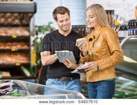 Couple using digital tablet while checking ingredients of product at butcher's shop