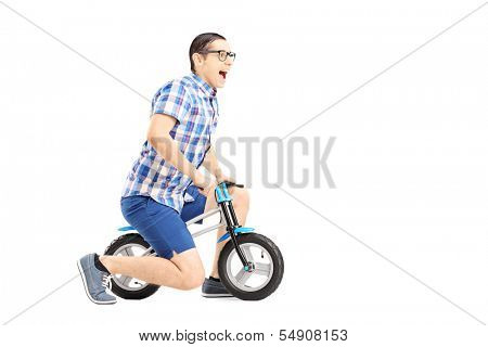 Excited guy riding a small bicycle isolated on white background