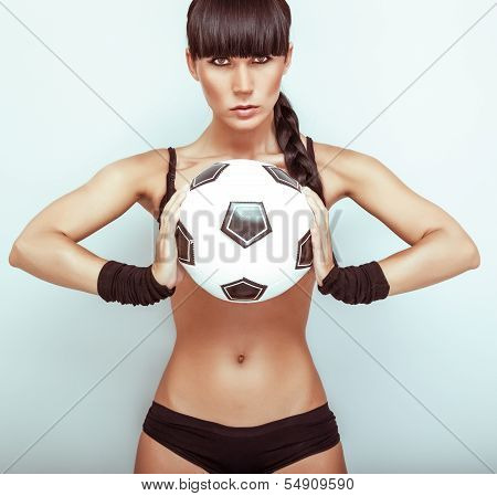 Portrait of a hot young female holding a soccerball