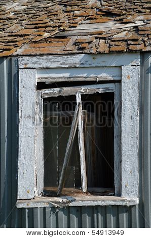 Broken window on a dilapidated steel shed